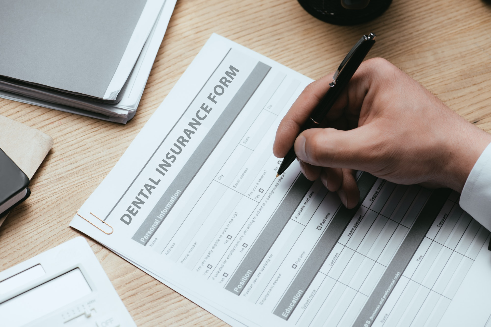 cropped view of man filling in Dental Insurance Form Dentist Concept
