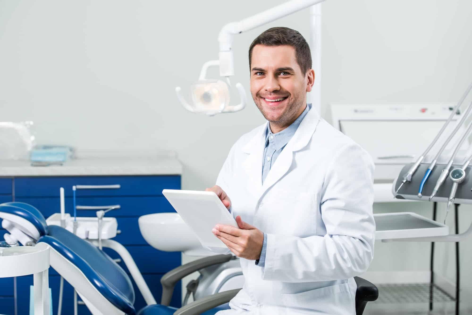 happy dentist in white coat holding digital tablet in dental clinic
